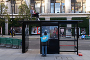 As the UK reacts to Prime Minister Boris Johnson's announcement of Lockdown 2 during the second wave of the Coronavirus pandemic, a man sits in a chair on top of a bus shelter on Oxford Street, on 2nd November 2020, in London, England.