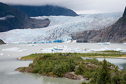 Visitors to Mendenhall Glacier near Juneau, Alaska hike the short and easy Photo Point Trail for a look at icebergs from the Mendenhall Glacier. The glacier descends from the massive Juneau Icefield into Mendenhall Lake. Mendenhall Glacier is a popular spot for cruise ship passengers and it sees over 500,000 visitors a year.