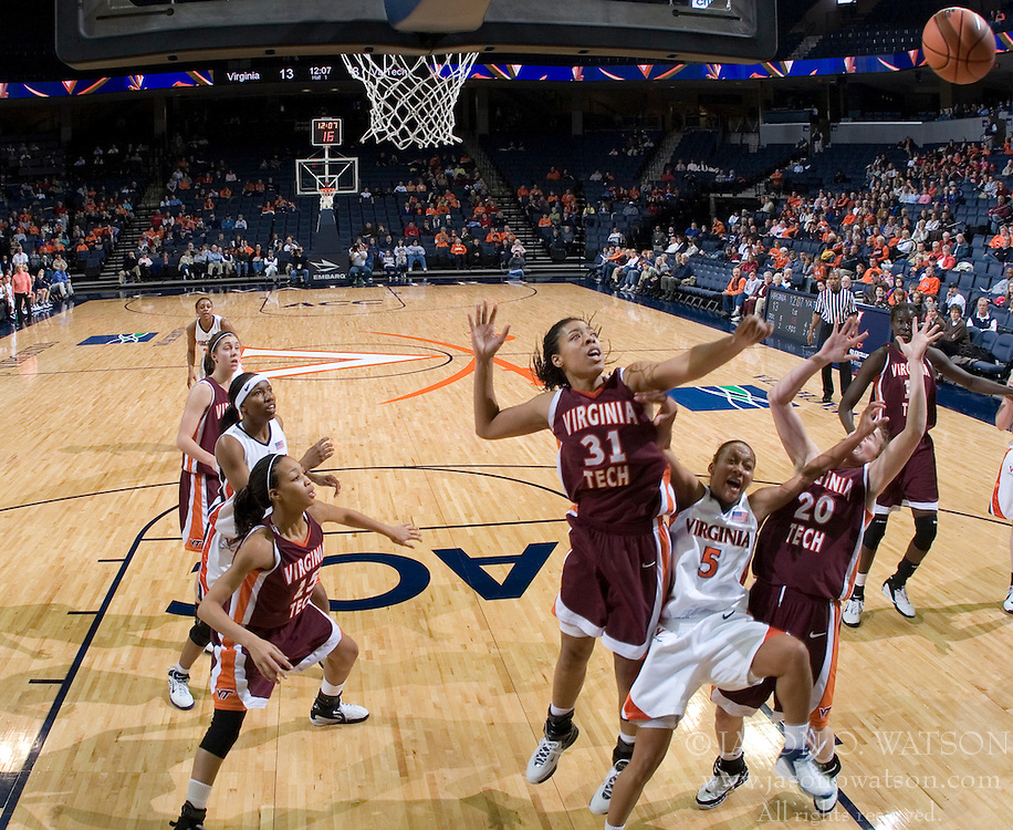 Virginia's Sharnee Zoll (5) is sandwiched by VT's Amber Hall (31) and Lindsay Biggs (20). The Virginia Tech Hokies overcame a 14 point Virginia lead to beat the Cavaliers 60-58 on their home court at the John Paul Jones Arena in Charlottesville, VA.