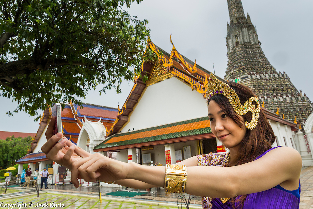 """23 SEPTEMBER 2013 - BANGKOK, THAILAND: A tourist dressed in a costume of the Royal Thai court circa 1800 takes pictures of herself with her iPhone in front of the central prang at Wat Arun. The outstanding feature of Wat Arun is its central prang (Khmer-style tower). The world-famous stupa will be closed for three years to undergo repairs and renovation along with other structures in the temple compound. This will be the biggest repair and renovation work on the stupa in the last 14 years. In the past, even while large-scale work was being done, the stupa used to remain open to tourists. It may be named """"Temple of the Dawn"""" because the first light of morning reflects off the surface of the temple with a pearly iridescence. The height is reported by different sources as between 66,80 meters and 86 meters. The corners are marked by 4 smaller satellite prangs. The temple was built in the days of Thailand's ancient capital of Ayutthaya and originally known as Wat Makok (The Olive Temple). King Rama IV gave the temple the present name Wat Arunratchawararam. Wat Arun officially ordained its first westerner, an American, in 2005. The central prang symbolizes Mount Meru of the Indian cosmology. The temple's distinctive silhouette is the logo of the Tourism Authority of Thailand.           PHOTO BY JACK KURTZ"""