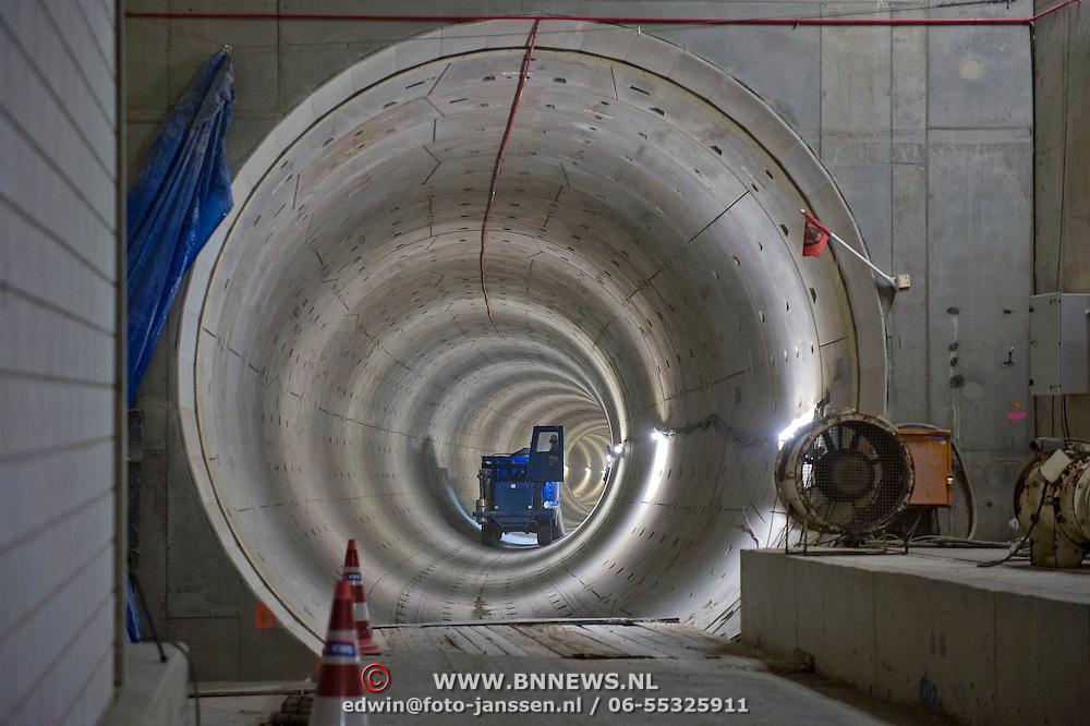 Een truck volgeladen met beton rijdt door de ronde en nog niet geplaveide vloer van de Noord Zuid tunnel naar de Paver, een reusachtige machine die het betonbed legt in de tunnel.