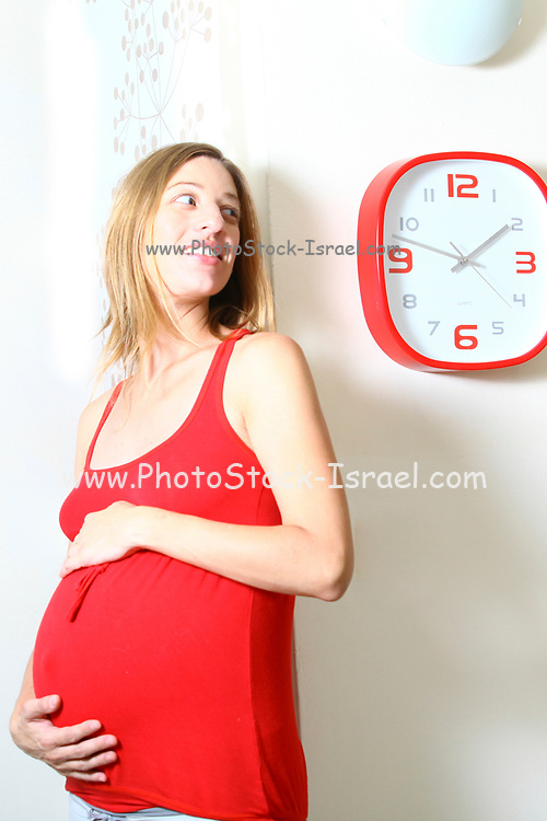 pregnant woman (nine months) looks expectantly at a clock. Model Release Available