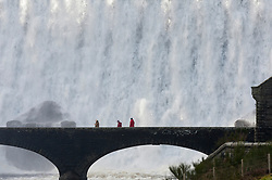 © Licensed to London News Pictures. 11/02/2019. Elan Valley, Powys, Wales, UK. Visitors walk across a bridge as water cascades over the Caban-coch dam, at Elan Valley village near Rhayader in Powys, Wales, UK after recent torrential rain in Powys has filled the complex of Elan valley dams and taken river levels to the tops of river banks in Powys, Wales, UK. Elan Valley dams supply Birmingham in the West Midlands UK with water via a gravity feed. credit: Graham M. Lawrence/LNP
