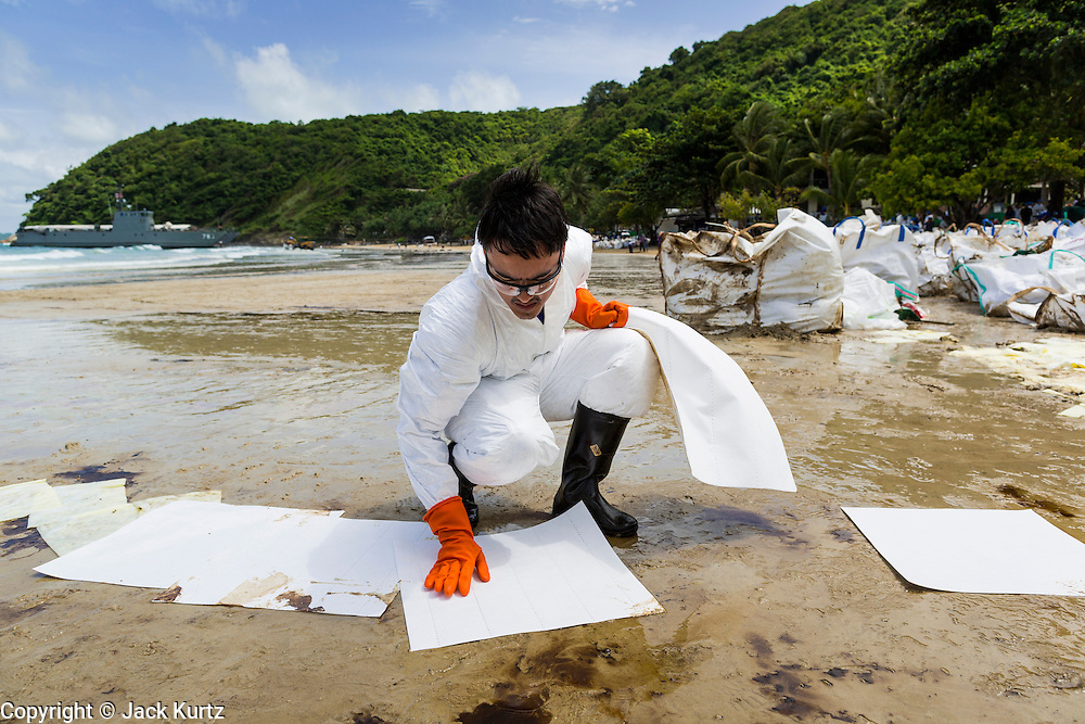 02 AUGUST 2013 - KOH SAMET, RAYONG, THAILAND: A cleanup worker places absorption pads on the beach to soak up oil on Ao Prao beach on Koh Samet island. About 50,000 liters of crude oil poured out of a pipeline in the Gulf of Thailand over the weekend authorities said. The oil made landfall on the white sand beaches of Ao Prao, on Koh Samet, a popular tourist destination in Rayong province about 2.5 hours southeast of Bangkok. Workers from PTT Global, owner of the pipeline, up to 500 Thai military personnel and volunteers are cleaning up the beaches. Tourists staying near the spill, which fouled Ao Prao beach, were evacuated to hotels on the east side of the island, which was not impacted by the spill. Officials have not said when Ao Prao beach would reopen. PTT Global Chemical Pcl is part of state-controlled PTT Pcl, Thailand's biggest energy firm.    PHOTO BY JACK KURTZ