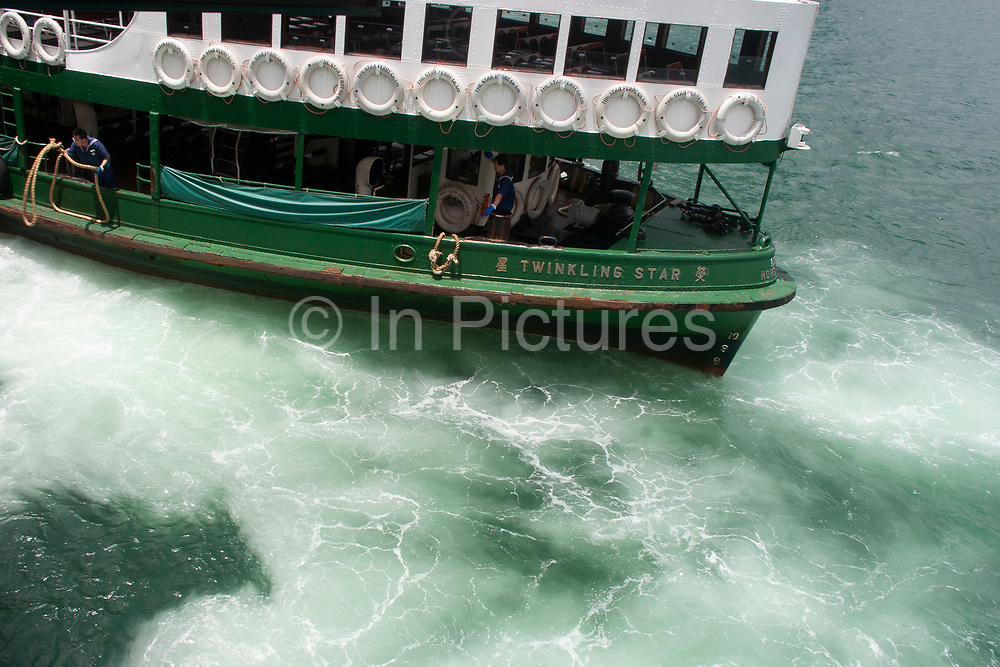 Star Ferry 'Twinkling Star's' engines stirs up the water as it comes in to dock at Hung Hom ferry terminal in Kowloon, Hong Kong, China. Founded in the late 1800's the Star Ferry Company still runs today and is one of Hong Kong's most classic sights, much like Red Buses in London. There are various services which run from different points on the Kowloon side and Hong Kong Island.
