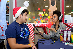 Volunteer Justino Bahamonde, 18, is interviewed by WHYY's Taylor Allen during the winter fest celebration at the Free Library branch in Olney, on December 16, 2018. (Bastiaan Slabbers for WHYY)