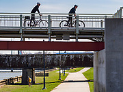 "01 APRIL 2020 - DES MOINES, IOWA: Bicyclists practice ""social distancing"" while they cross a bridge over the Des Moines River on a warm spring day in downtown Des Moines. Despite the pleasant weather, many people stayed indoors because the coronavirus (SARS-CoV-2) pandemic. On Saturday morning, 04 April, Iowa reported 786 confirmed cases of the Novel Coronavirus (SARS-CoV-2) and COVID-19. There have been 14 deaths attributed to COVID-19 in Iowa. Restaurants, bars, movie theaters, places that draw crowds are closed until 30 April. The Governor has not ordered ""shelter in place"" but several Mayors, including the Mayor of Des Moines, have asked residents to stay in their homes for all but the essential needs. People are being encouraged to practice ""social distancing"" and many businesses are requiring or encouraging employees to telecommute.         PHOTO BY JACK KURTZ"