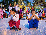 28 OCTOBER 2015 - YANGON, MYANMAR: Men pray at a statue of the Buddha during observances of Thadingyut at Botataung Pagoda in Yangon. Botataung Pagoda was first built by the Mon, a Burmese ethnic minority, around the same time as was Shwedagon Pagoda, over 2500 years ago. The Thadingyut Festival, the Lighting Festival of Myanmar, is held on the full moon day of the Burmese Lunar month of Thadingyut. As a custom, it is held at the end of the Buddhist lent (Vassa). The Thadingyut festival is the celebration to welcome the Buddha's descent from heaven.    PHOTO BY JACK KURTZ