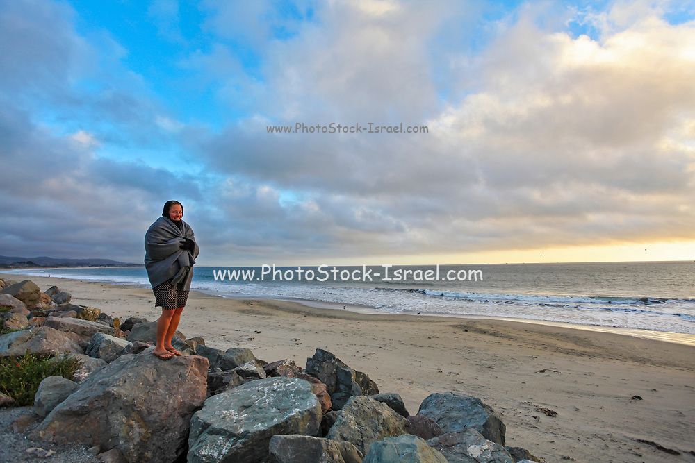 Young woman, wrapped in a blanket stands on the beach looking out to the ocean