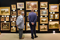 © Licensed to London News Pictures. 27/06/2017. London, UK.  A gallery owner meets a client at The Arts & Antiques Fair taking place at Olympia in Kensington.  The event is the UK's largest and most established art and antiques fair and runs until 2 July. Photo credit : Stephen Chung/LNP