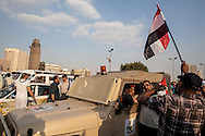 Anti government demonstrators pose for photos on a Egyptian military car as it passes through a street demonstration in downtown Cairo, Egypt.