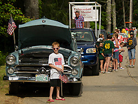 A boy stands in front of a 1952 Ford as folks line up along High Street for the Gilmanton 4th of July parade marching through four corners.  (Karen Bobotas Photographer)