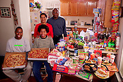 The Revis family in the kitchen of their home in suburban Raleigh, North Carolina, with a week's worth of food. Ronald Revis, and Rosemary Revis, stand behind Rosemary's sons from her first marriage, Brandon Demery, (left), and Tyrone Demery. From the book Hungry Planet: What the World Eats (Model Released)