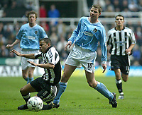 Photo. Andrew Unwin.<br /> Newcastle United v Manchester City, Barclaycard Premier League, St James' Park, Newcastle upon Tyne 22/11/2003.<br /> Newcastle's Jermaine Jenas (l) is brought down by City's Michael Tarnat (r).