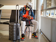 """17 MARCH 2020 - DES MOINES, IOWA:  PATRICK AWO, from Des Moines, cleans his hands with sanitizer after flying into Des Moines International Airport Tuesday. The airport was almost empty as air travel is greatly reduced because of the Coronavirus outbreak. Sunday night, the Governor of Iowa announced that the state health department had recorded """"community spread"""" in Des Moines. Tuesday, the Governor ordered all restaurants and bars to close or transition to take out only. The Iowa Department of Public Health has urged all public buildings, like libraries and schools, to close, and all schools in Iowa are closed for at least 30 days.    PHOTO BY JACK KURTZ"""