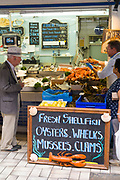 Customers shopping at popular Dunn-Ross Fisheries fish stall at Beresford Street Market, St Helier, Jersey, Channel Isles