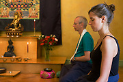 Buddhists meditate in silence for 30 minutes in their Shrine Room at the Rivendell Buddhist Retreat Centre, England. A middle-aged man and a younger woman sit in a meditative cross-legged position in order to relax their bodies and free their minds for this period of inner-contemplation. Their retreat centre is a Victorian house now run by the Triratna Buddhist Community. Once a Victorian country rectory for the local vicar in this East Sussex village, it now houses facilities for the spiritual and the peaceful, having escaped for a brief time, the pressures of modern life. Beyond are two Buddhas on a tapestry and as a statue. The community web address is www.rivendellretreatcentre.com.