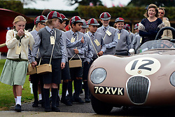 © Licensed to London News Pictures. 13/09/2013. Chichester, UK School children from March School dressed as wartime evacuees look at a car as it passes by. People enjoy the atmosphere at the 2013 Goodwood Revival. The event recreates the glorious days of motor racing and participants are encouraged to dress in period dress. The revival is the only event of its kind to be staged entirely in the nostalgic time capsule of the 1940s, 50s and 60s Photo credit : Stephen Simpson/LNP.