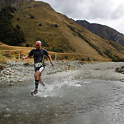 Runner Ami Arami crosses Moke Creek on the Ben Lomond High Country Station during the Pure South Shotover Moonlight Mountain Marathon and trail runs. Moke Lake, Queenstown, New Zealand. 4th February 2012. Photo Tim Clayton