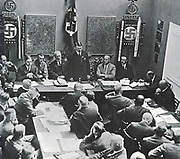 Hitler in Munich adressing a meeting of the NSDAP in 1925. Third to the left of Hitler is Alfred Rosenberg, on the right are Gregor Strasser and Heinrich Himmler. Far right by the door is Julius Streicher.