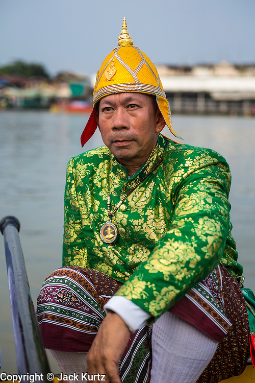 06 NOVEMBER 2012 - BANGKOK, THAILAND:  A steersmen relaxes on Royal Barge at the barge landing at Wat Arun after the final dress rehearsal for the Royal Barge Procession. Thailand's Royal Barge Procession has both religious and royal significance. The tradition is nearly 700 years old. The Royal Barge Procession takes place rarely, typically coinciding with only the most important cultural and religious events. During the reign of King Bhumibol Adulyadej, spanning over 60 years, the Procession has only occurred 16 times. The Royal Barge Procession consists of 52 barges: 51 historical Barges, and the Royal Barge, the Narai Song Suban, which King Rama IX built in 1994. It is the only Barge built during King Bhumibol's reign. These barges are manned by 2,082 oarsmen. The Procession proceeds down the Chao Phraya River, from the Wasukri Royal Landing Place in Bangkok, passes the Grand Palace complex and ends at Wat Arun. Tuesday's dress rehearsal was the final practice for the 2012 Royal Barge Procession, which takes place November 9.     PHOTO BY JACK KURTZ