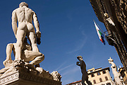 "The giant nudes of Baccio Bandinelli's Hercules & Cacus and Michelangelo's David stand in Piazza della Signoria beneath the fortress palace Palazzo Vecchio. Piazza della Signoria is an L-shaped square in front of the Palazzo Vecchio (""Old Palace"") which is the town hall of the city. This massive, Romanesque, crenulated fortress-palace is among the most impressive town halls of Tuscany. Overlooking the square with its copy of Michelangelo's David statue as well the gallery of statues in the adjacent Loggia dei Lanzi, it is one of the most significant public places in Italy, and it host cultural points and museums."