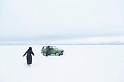 Couple crossing frozen lake, Severobaikalsk, Lake Baikal. Siberia, Russia