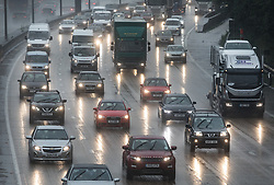 © Licensed to London News Pictures. 09/08/2017. Banstead, UK. Traffic heads clockwise on the M-25 in Surrey near Reigate as heavy downpours continue into the afternoon. Bands of heavy unseasonal rain are crossing the UK. Photo credit: Peter Macdiarmid/LNP
