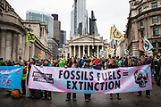 Activists sing and hold banners outsidethe Bank of England during a protest in the City of London, on 14th October 2019. Hundreds of activists blocked roads  in the financial district on Monday, calling out the financial sectors funding of fossil fuels around the world.