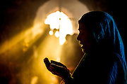 """2nd April 2015, New Delhi, India. Sunlight streams through an arched doorway as a woman prays at a shrine dedicated to Djinn worship in the ruins of Feroz Shah Kotla in New Delhi, India on the 2nd April 2015<br /> <br /> PHOTOGRAPH BY AND COPYRIGHT OF SIMON DE TREY-WHITE a photographer in delhi<br /> + 91 98103 99809. Email: simon@simondetreywhite.com<br /> <br /> People have been coming to Firoz Shah Kotla to leave written notes and offerings for Djinns in the hopes of getting wishes granted since the late 1970's. Jinn, jann or djinn are supernatural creatures in Islamic mythology as well as pre-Islamic Arabian mythology. They are mentioned frequently in the Quran  and other Islamic texts and inhabit an unseen world called Djinnestan. In Islamic theology jinn are said to be creatures with free will, made from smokeless fire by Allah as humans were made of clay, among other things. According to the Quran, jinn have free will, and Iblis abused this freedom in front of Allah by refusing to bow to Adam when Allah ordered angels and jinn to do so. For disobeying Allah, Iblis was expelled from Paradise and called """"Shaytan"""" (Satan).They are usually invisible to humans, but humans do appear clearly to jinn, as they can possess them. Like humans, jinn will also be judged on the Day of Judgment and will be sent to Paradise or Hell according to their deeds. Feroz Shah Tughlaq (r. 1351–88), the Sultan of Delhi, established the fortified city of Ferozabad in 1354, as the new capital of the Delhi Sultanate, and included in it the site of the present Feroz Shah Kotla. Kotla literally means fortress or citadel."""