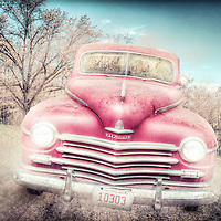 High dynamic range composite image.  Vintage Plymouth truck with lit headlights and spirit driver, kicking up dust on mountain road.
