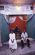 Local Hispah Sharia police offices. From here the volunteer police force recruits new members and surveys the neighborhood for anything considered non-Sharia..The implementation of Islamic Sharia Law across the twelve northern states of Nigeria, centres upon Kano, the largest Muslim Husa city, under the feudal, political and economic rule of the Emir of Kano. Islamic Sharia Law is enforced by official state apparatus including military and police, Islamic schools and education, plus various volunteer Militia groups supported financially and politically by the Emir and other business and political bodies. Fanatical Islamic Sharia religious traditions  are enforced by the Hispah Sharia police. Deliquancy is controlled by the Vigilantes volunteer Militia. Activities such as Animist Pagan Voodoo ceremonies, playing music, drinking and gambling, normally outlawed under Sharia law exist as many parts of the rural and urban areas are controlled by local Mafia, ghetto gangs and rural hunters. The fight for control is never ending between the Emir, government forces, the Mafia and independent militias and gangs. This is fueled by rising petrol costs, and that 70% of the population live below the poverty line. Kano, Kano State, Northern Nigeria, Africa