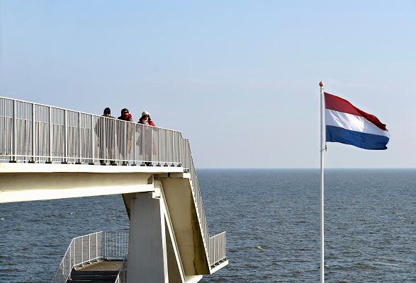 Nederland, the Netherlands, Kornwerderzand, 22-2-2018 De Afsluitdijk zal de komende jaren aanpassingen krijgen om de verwachte zeespiegelstijging en extreem weer het hoofd te kunnen bieden . Het Vlietermonument bevindt zich bij de Vlieter, de plaats waar in 1932 de Afsluitdijk werd gesloten. Het is een monument in de vorm van een uitkijktoren, ontworpen door architect Willem Dudok. De toren is in 1933 gebouwd . Het standbeeld van de steenzetter, dijkwerker, is van latere datum .Foto: Flip Franssen