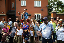 © Licensed to London News Pictures . 11/08/2018. Manchester , UK . People gather on the streets to watch the parade pass through Moss Side . The annual Moss Side Caribbean Carnival procession , celebrating dance , music and Afro-Caribbean culture , which passes in a loop from Alexandra Park and through the streets of Moss Side . Photo credit : Joel Goodman/LNP