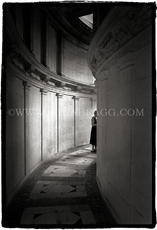 Black and white photo of a woman in a hallway in a cathedral in Seville, Spain.