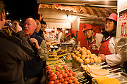 Tourists try Chinese snacks in the Night Market, Wangfujing Street, Beijing, China