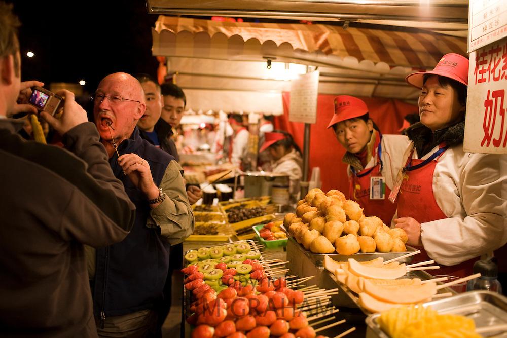 Tourists try Chinese snacks in the Night Market, Wangfujing Street, Beijing, China