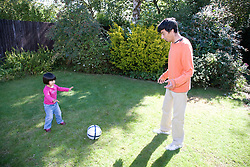 Little girl and her father playing football in the garden,