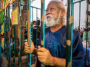 """06 JULY 2015 - BANGKOK, THAILAND: A human rights activist in a mock jail cell to call attention to the plight of students arrested for charges related to political assembly. More than 100 people gathered at Thammasat University in Bangkok Monday to show support for 14 students arrested two weeks ago. The students were arrested for violating orders against political assembly. They face criminal trial in military courts. The students' supporters are putting up """"Post It"""" notes around Bangkok and college campuses up country calling for the students' release.      PHOTO BY JACK KURTZ"""