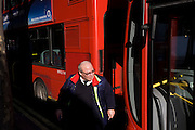 A Go Ahead London bus driver between two of his company's vehicles in a central London street.