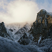Last sunlight on the mountain with low hanging clouds in valley de Chaudefour. With Unidentified trees covered with frost and some snow.