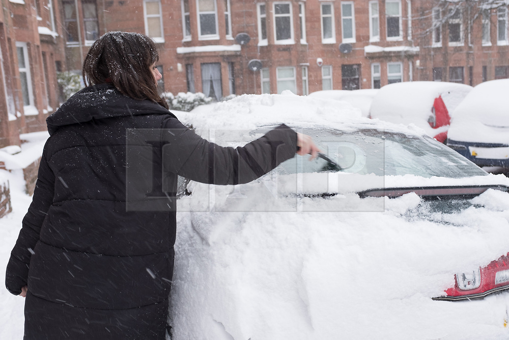"""© Licensed to London News Pictures. 28/02/2018. <br /> <br /> A woman deices her car in Springhill Gardens, Shawlands, Glasgow, Scotland as the city hit with snow storm """"Beast from the East"""" on 28th February 2018.<br /> <br /> Photo credit should read Max Bryan/LNP"""