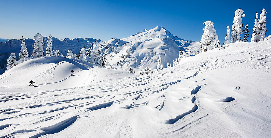 Skiers travel over the wind swept snow of Artist Point, a scenic viewpoint and popular destination in the Washington Cascades. Mount Baker is visible in the distance.