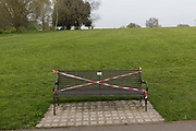 As the UK Prime Minister Boris Johnson suffers from Coronavirus and remains in intensive care in hospital - with a record 938 UK daily deaths recorded, a total of 7,097, benches are taped to stop the public from using them, in Brockwell Park that was recently closed after 3,000 park users forced Lambeth council to completely close the south London green space, on 8th April 2020, in south London, England.
