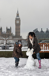 © licensed to London News Pictures. London, UK 05/02/12. Two Children making a snowman outside St Thomas's Hospital in Westminster in front of The Houses of Parliament, after snow sweept across London on February 5th, 2012. Photo credit: Tolga Akmen/LNP