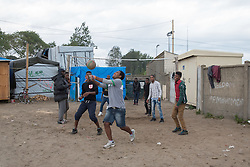 """Calais, Pas-de-Calais, France - 16.10.2016    <br />     <br />  Some refugees playing volleyball. """"Jungle"""" refugee camp on the outskirts of the French city of Calais. Many thousands of migrants and refugees are waiting in some cases for years in the port city in the hope of being able to cross the English Channel to Britain. French authorities announced that they will shortly evict the camp where currently up to up to 10,000 people live.<br /> <br /> Einige Fluechtlinge spielen Volleyball. """"Jungle"""" Fluechtlingscamp am Rande der franzoesischen Stadt Calais. Viele tausend Migranten und Fluechtlinge harren teilweise seit Jahren in der Hafenstadt aus in der Hoffnung den Aermelkanal nach Großbritannien ueberqueren zu koennen. Die franzoesischen Behoerden kuendigten an, dass sie das Camp, indem derzeit bis zu bis zu 10.000 Menschen leben Kürze raeumen werden. <br /> <br /> Photo: Bjoern Kietzmann"""