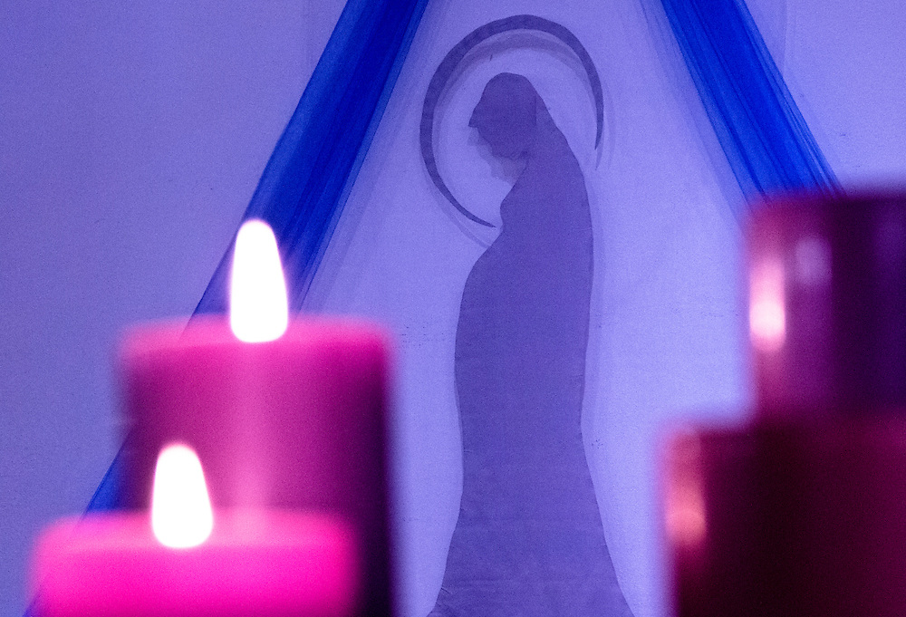 Mary, Mother of Jesus, is depicted pregnant between two sets of candles.