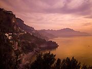 A beautiful sunset turns this view of the Amalfi Coast purple and orange