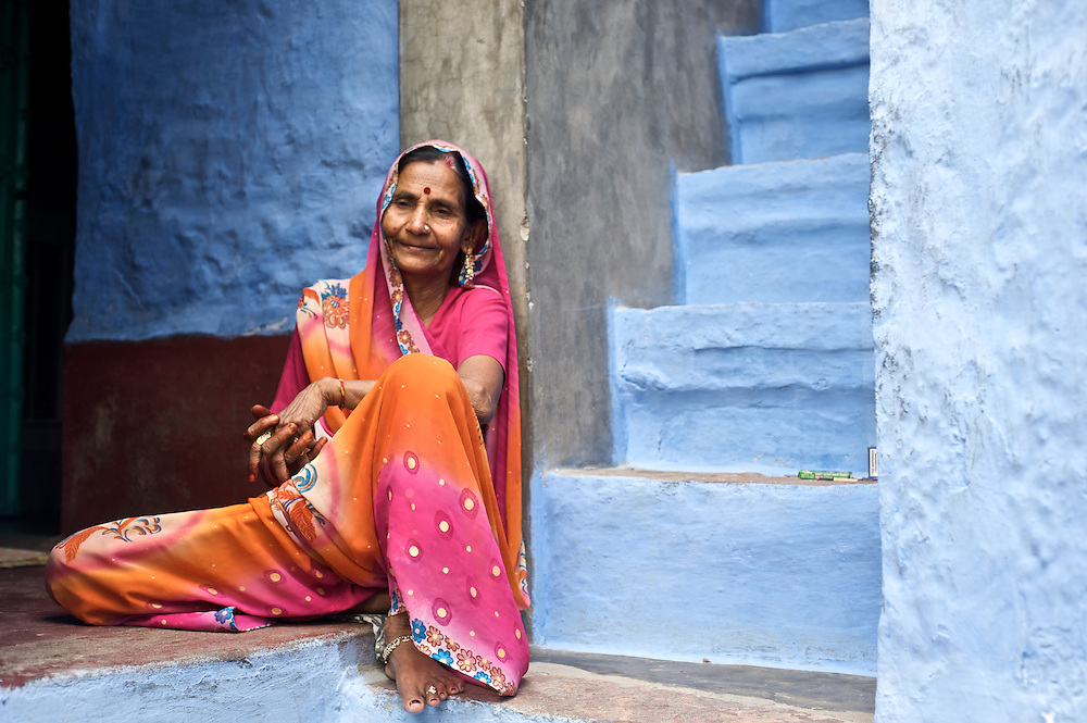 """Johpur is known as """"The Blue City"""" due to the Brahman neighborhoods being painted in blue.  The blue is an historic color for Brahman homes that most of the city adopted.  It is said to keep the mosquitoes at bay and the temperatures cooler.  Here a woman in a colorful sari relaxes at her home."""