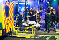 © Licensed to London News Pictures . 27/12/2016 . Wigan , UK . People watch as a woman is wheeled on a trolley on to the back of an ambulance . Revellers in Wigan enjoy Boxing Day drinks and clubbing in Wigan Wallgate . In recent years a tradition has been established in which people go out wearing fancy-dress costumes on Boxing Day night . Photo credit : Joel Goodman/LNP